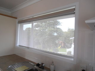 Sunscreen blind with blockout blind rolled away